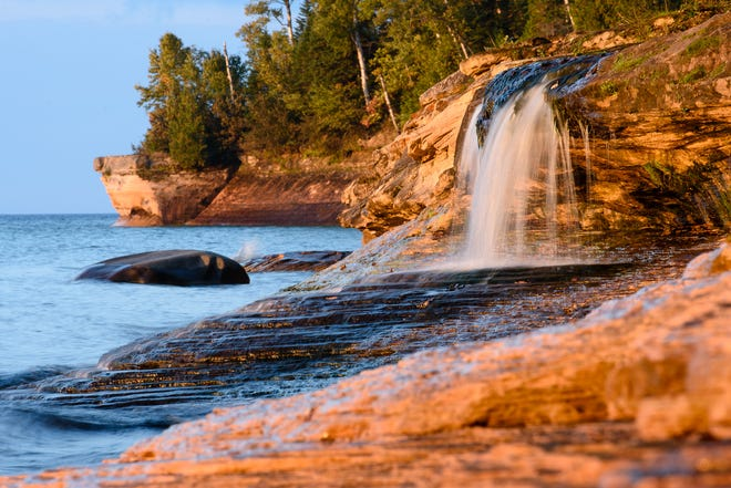 Going to Elliot Falls, aka Miners Beach Falls, at sunset is popular among visitors to Pictured Rocks National Lakeshore Park, to watch the color of the rocks change into golden-brown tones.