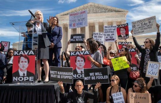 Sen. Kirsten Gillibrand, D-N.Y., left, and Sen. Kamala Harris, D-Calif., speak as protesters rally against Supreme Court nominee Brett Kavanaugh as the Senate Judiciary Committee debates his confirmation Friday.