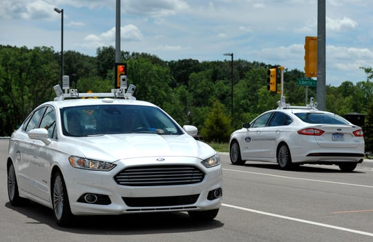 Two Ford autonomous vehicles pass each other during a demonstration where autonomous vehicles interact with pedestrians, bicyclists and driven vehicles, June 21, 2017, on the Mcity track at the University of Michigan's North Campus in Ann Arbor.