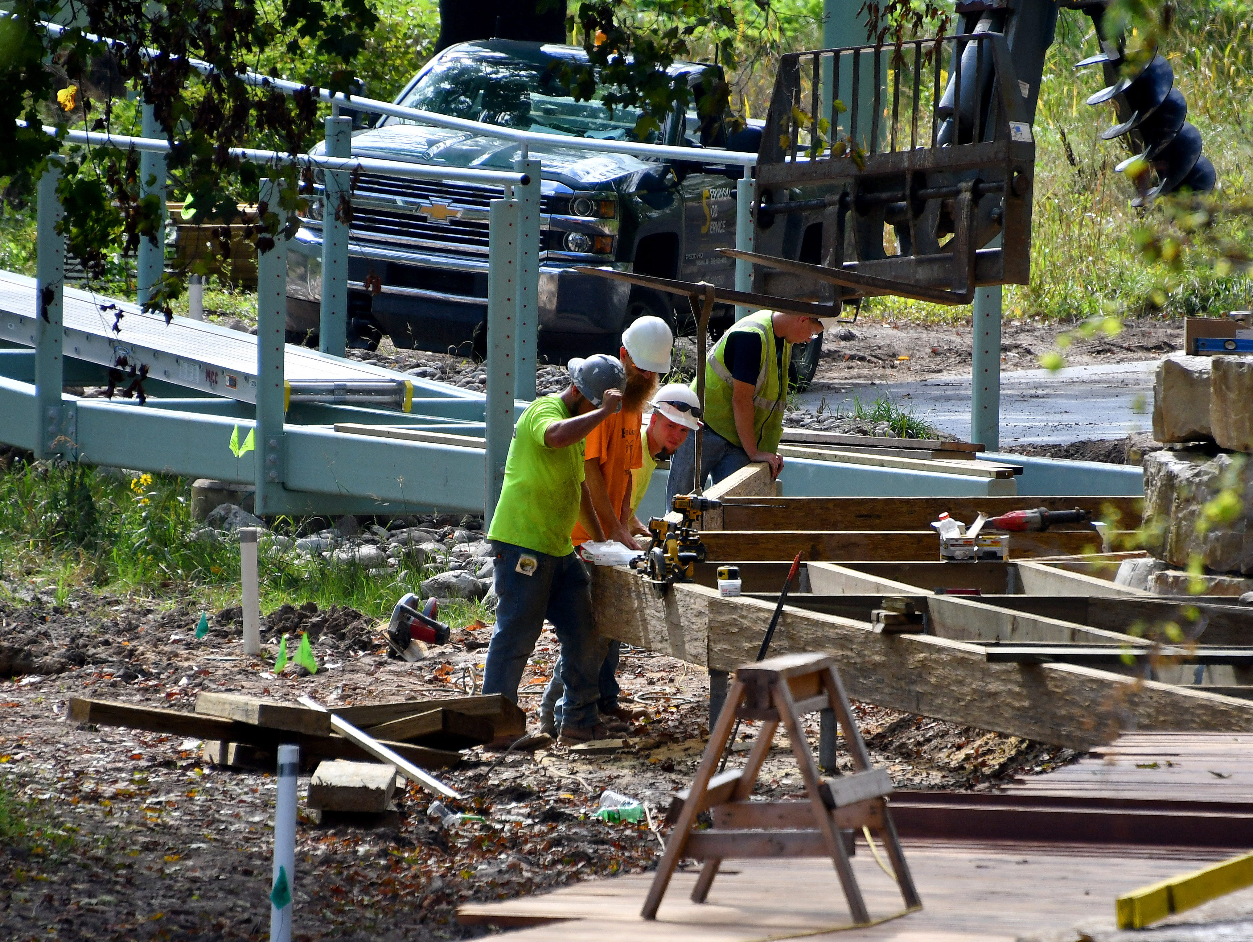 Workers in Whiting Forest build a board walk to connect with a pedestrian bridge that will span St. Andrews Road and link Whiting Forest with Dow Gardens.