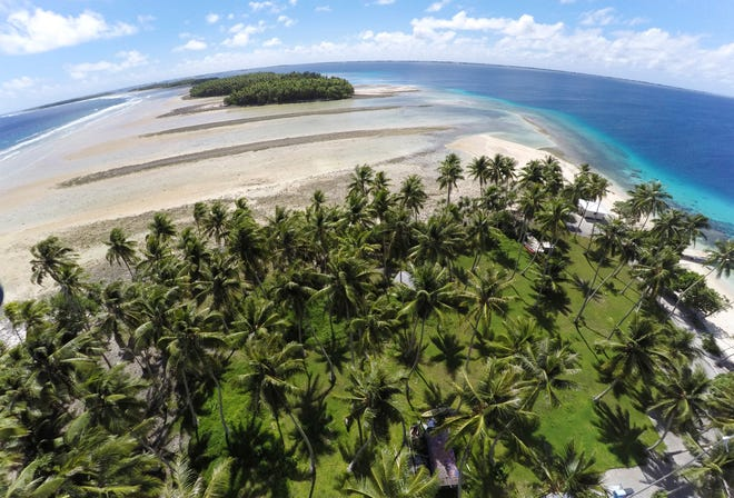 This Nov. 6, 2015, file photo, shows a large section of land between the trees washed away due to continuing rising sea leaves on Majuro Atoll, Marshall Islands.