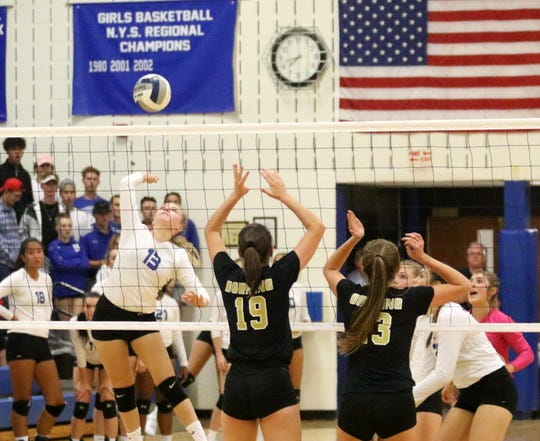 Peyton Knapp of Horseheads goes up for a spike as Corning's Taylor Slavin (19) and Lauren Ball (13) get set to defend Sept. 27, 2018 at Horseheads Middle School.