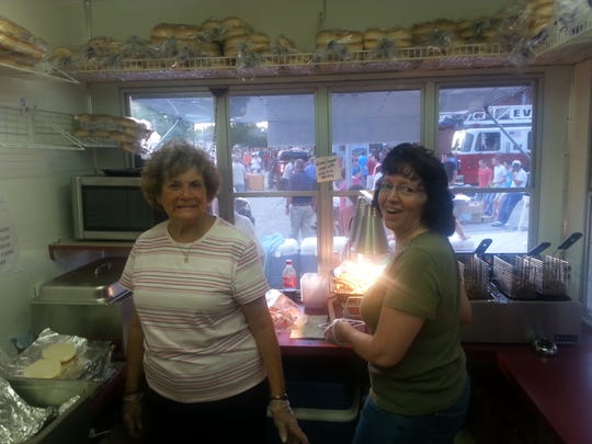 Volunteers prepare food at the Central United Methodist church booth. The booth has been a mainstay at the West Side Nut Club Fall Festival since the early 90s.