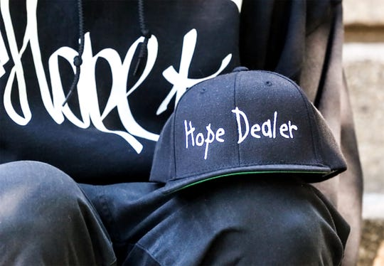 """Nathan Scheer of Fond du Lac, Wisconsin made hats for himself and son Bentley that say """"Hope Dealer."""" Nathan is a recovering heroin addict that now spends his free time doing good things for his community. Bentley is his partner in cleaning up the community. Doug Raflik/USA TODAY NETWORK-Wisconsin"""