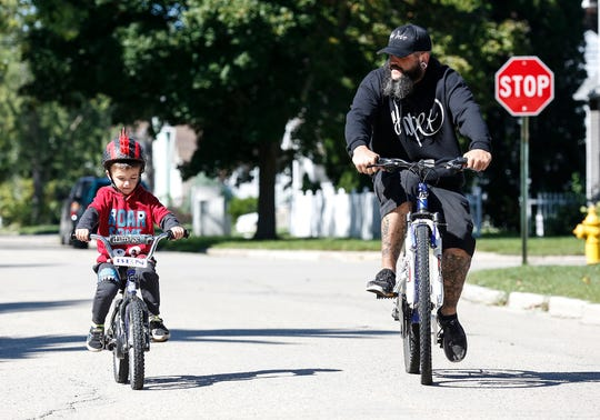 Nathan Scheer rides a bike with his 5-year-old son Bentley The duo will often ride around, picking up trash along streets, in playgrounds and parks. Scheer , a recovering heroin addict, says its his motivation to stay sober, cleaning up streets for kids. Saturday, September 22, 2018 in Fond du Lac, Wisconsin. Doug Raflik/USA TODAY NETWORK-Wisconsin