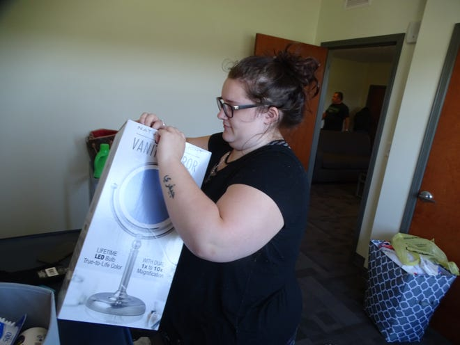Terra State Community College student Amber Strzesynski of Rossford moves into her room Friday at the Landings at Terra Village. The student housing facility opened Friday to more than 50 students, with Terra State being only the second community college in Ohio to have on-campus student housing.