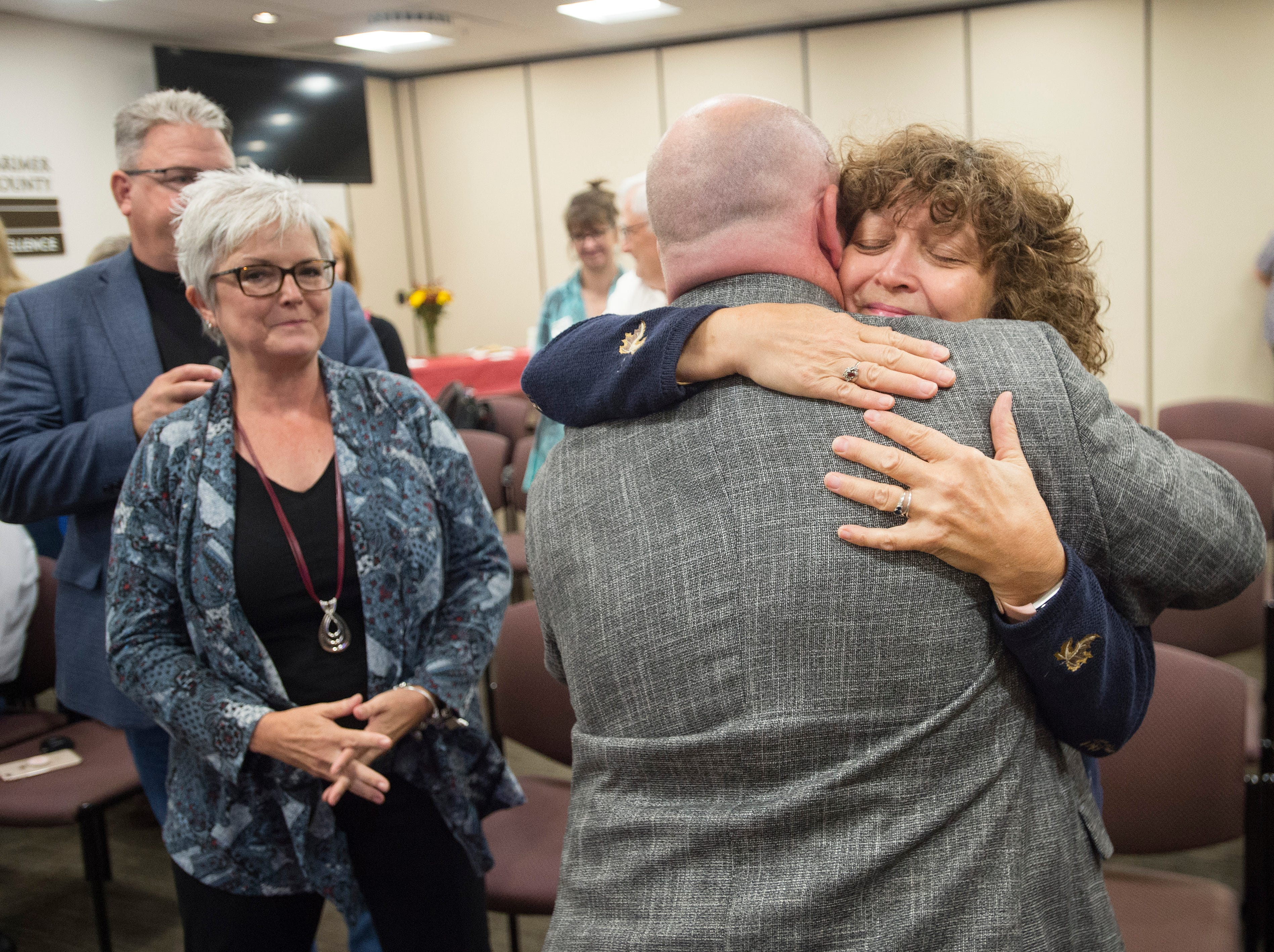 Jeannette Gaiter hugs Sean Dougherty after he is sworn in as Larimer County Commissioner on Friday, September 28, 2018. Dougherty was appointed to the position in the vacancy left by Lew Gaiter III after his death on September 18.