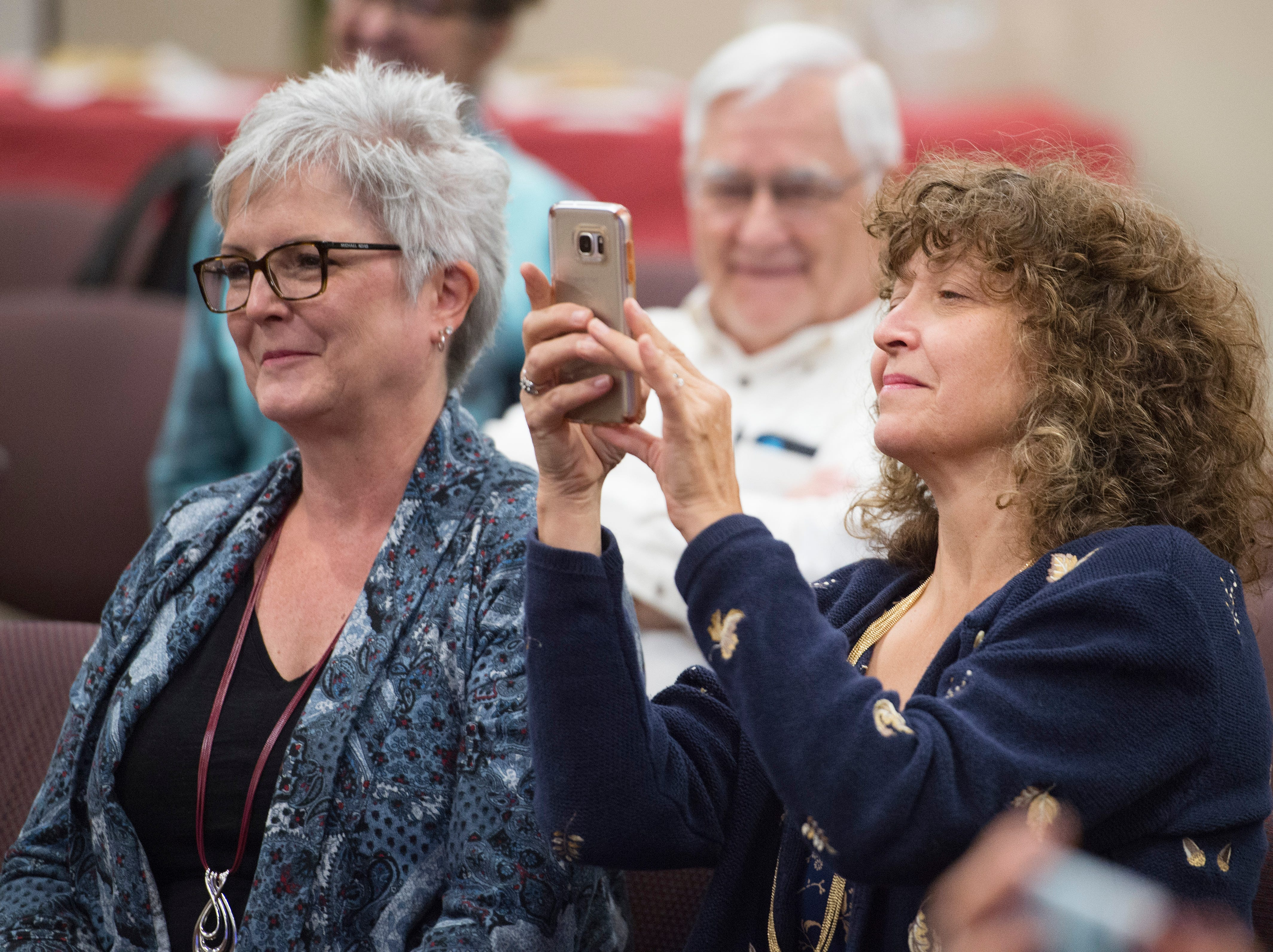 Jeannette Gaiter takes a photo with her cell phone as she sits next to Mary Dougherty as her husband, Sean, is sworn in as Larimer County Commissioner on Friday, September 28, 2018. Dougherty was appointed to the position in the vacancy left by Lew Gaiter III after his death on September 18.