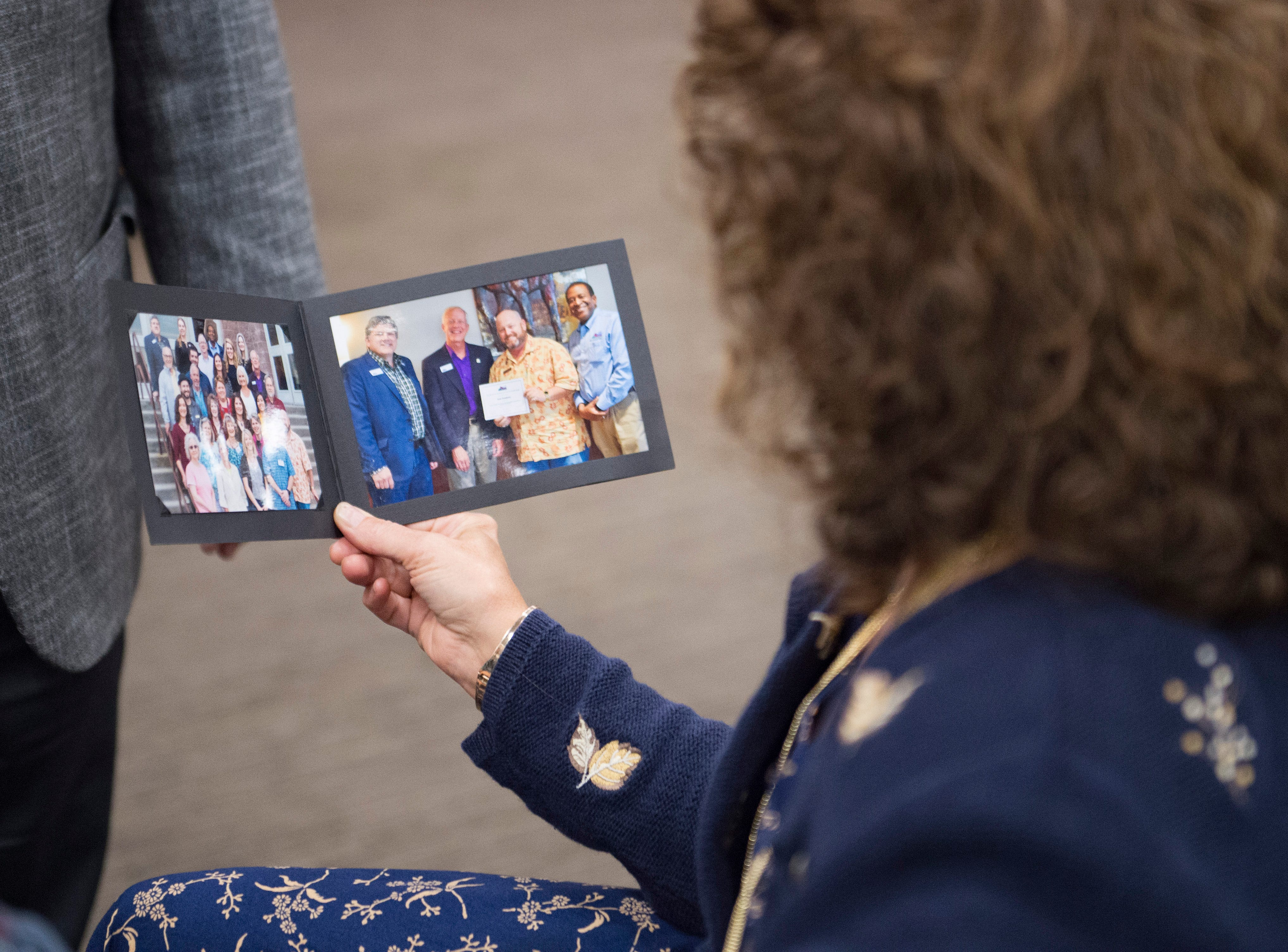 Jeannette Gaiter looks at a photo of Sean Dougherty with her late husband, Lew, before Dougherty is sworn in as Larimer County Commissioner on Friday, September 28, 2018. Dougherty was appointed to the position in the vacancy left by Lew Gaiter III after his death on September 18.