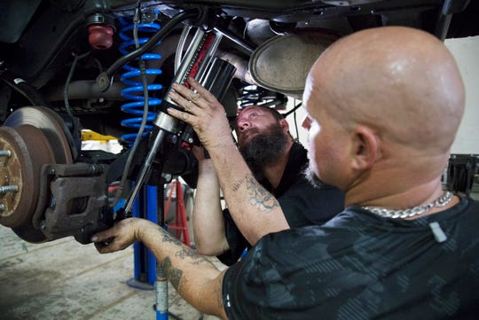 John Palmer, center, and Chris Schaffer work on the Jeep belonging to fallen Fort Myers Police officer Adam Jobbers-Miller on Thursday at Savage 4x4 Inc., in Fort Myers. The Jeep is being made over by volunteers as part of Savage's Hero Project. The project honors Jobbers-Miller and other fallen law enforcement officers.