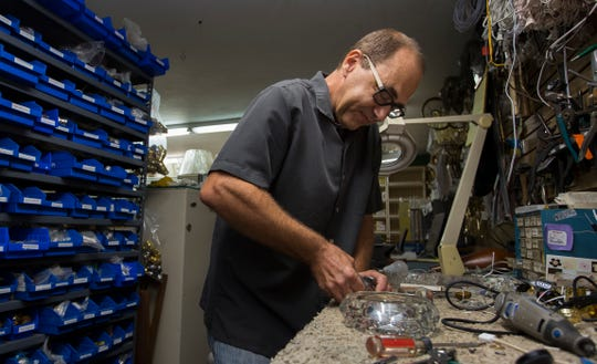 Jay Thisted, owner of TJ's Lamps & Shades, repairs a customer's lamp in his Cape Coral store.