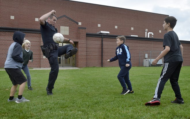 Sturgeon Bay Police Dept. officer Preston Hajny controls the ball in a quick game of soccer prior to the start of school at Sunrise Elementary on Friday, Sept. 28, 2018. Hajny and patrol partner Derek Jennerjohn's camaraderie with the schoolchildren before the morning bell has been embraced by parents and teachers.  Tina M. Gohr/USA TODAY NETWORK-Wisconsin