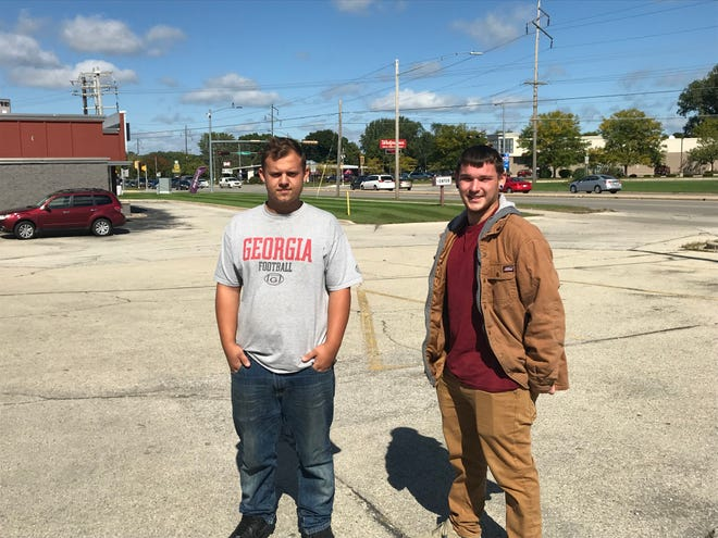 Justin Springfield andTyler Brickham stand near the intersection of East Mason and Main streets, where they helped rescue stranded drivers during flash floods earlier this month in Green Bay.