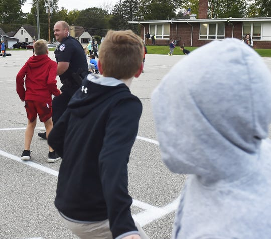 Sturgeon Bay Police Dept. officer Derek Jennerjohn looks for an opening while playing a pick-up game of basketball prior to the start of school at Sunrise Elementary School in Sturgeon Bay on Friday, Sept. 28, 2018.