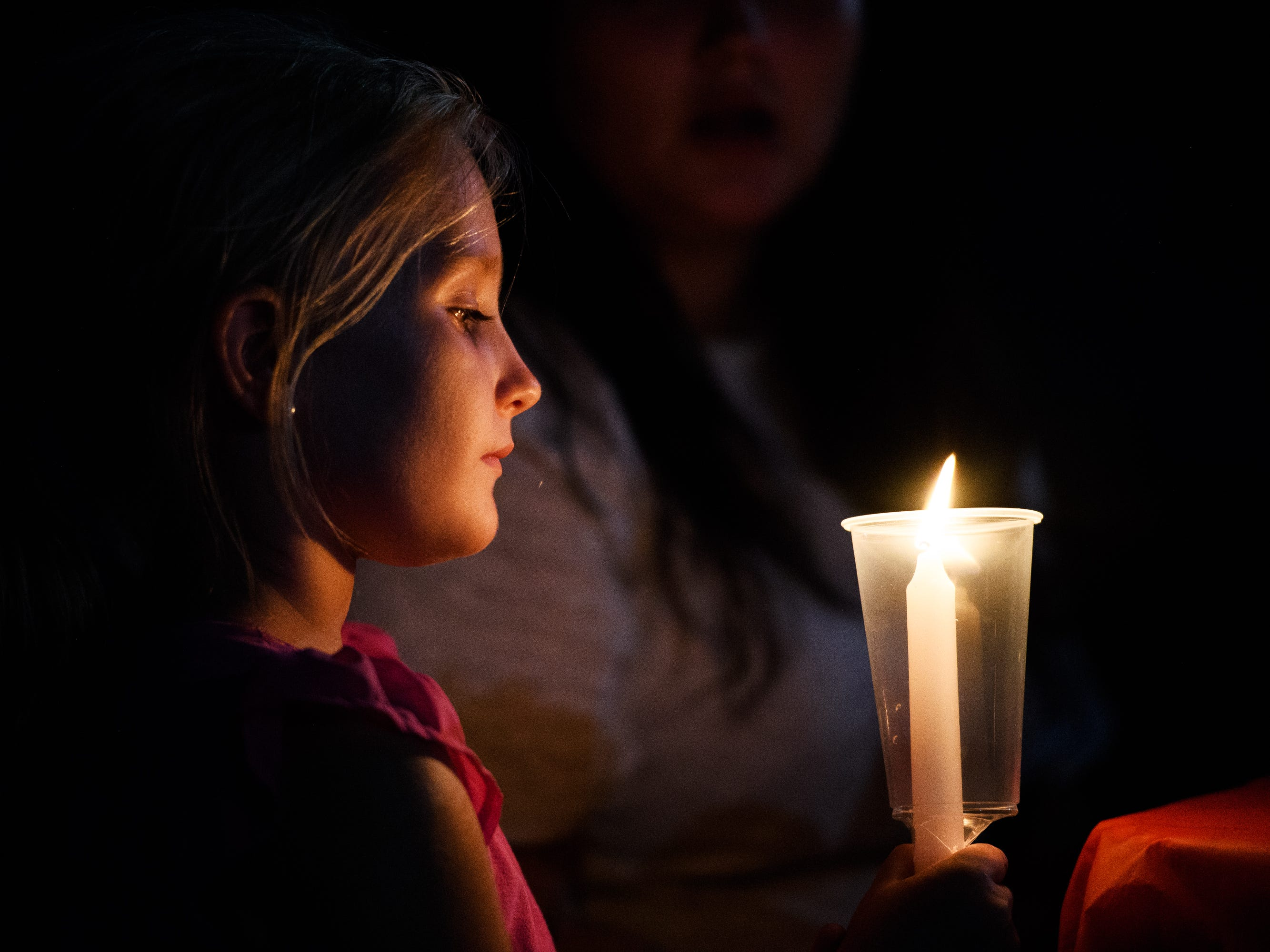 Madysen XXX, holds a candle during a vigil for her uncle, Jared Johns, at Simpsonville City Park on Sunday, Sept. 23, 2018.