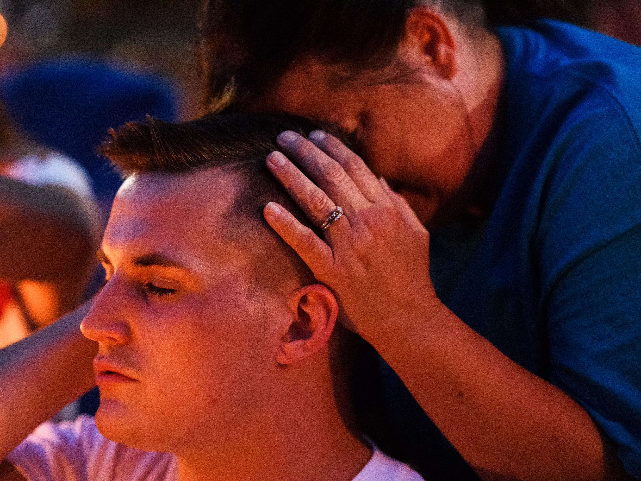 Kathy Bowling holds her son Jacob Johns during a candlelight vigil for her other son, Jared, at Simpsonville City Park on Sunday, Sept. 23, 2018.
