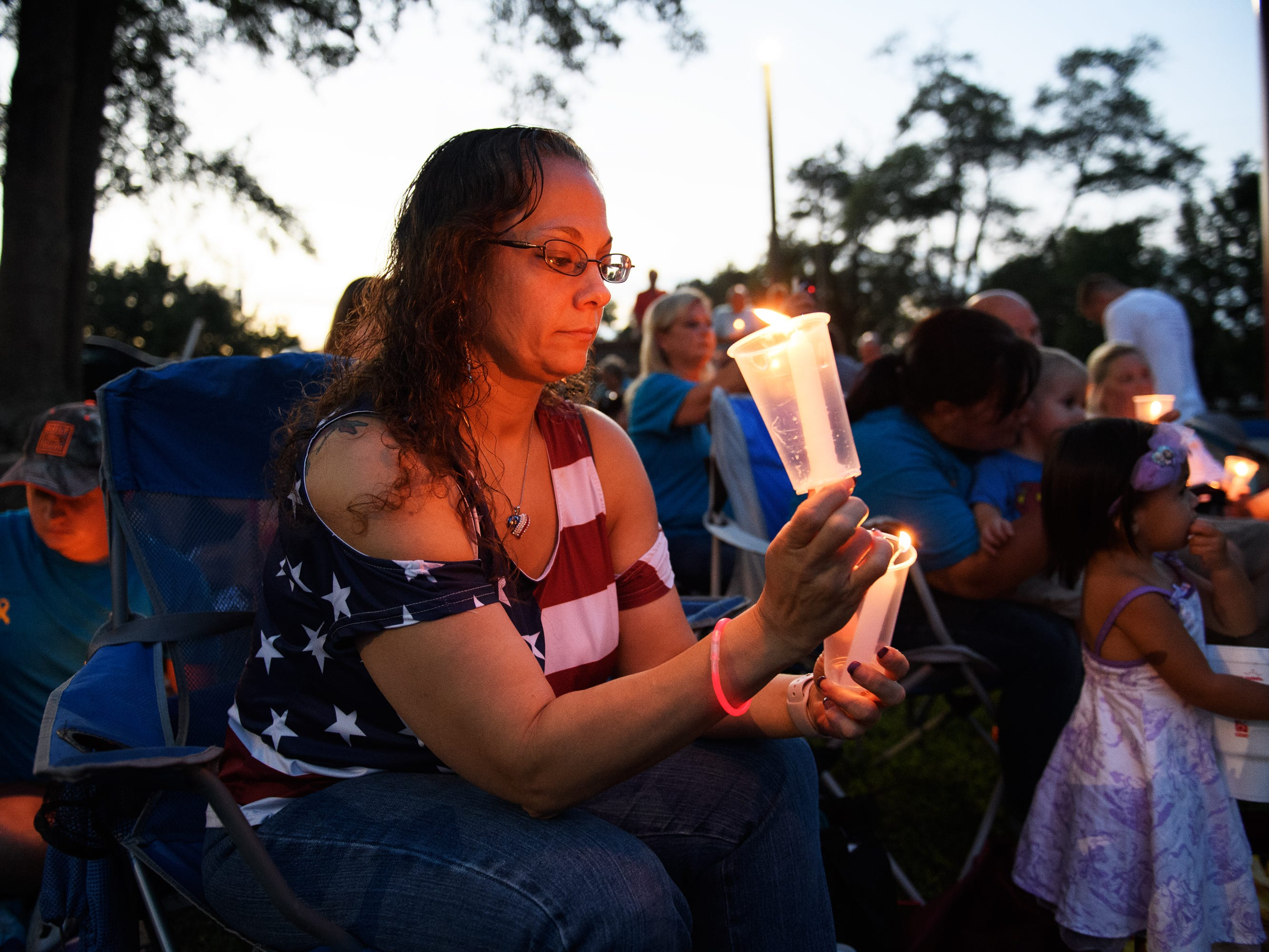 Lisa Jules lights candles during a vigil for Jared Johns at Simpsonville City Park on Sunday, Sept. 23, 2018.