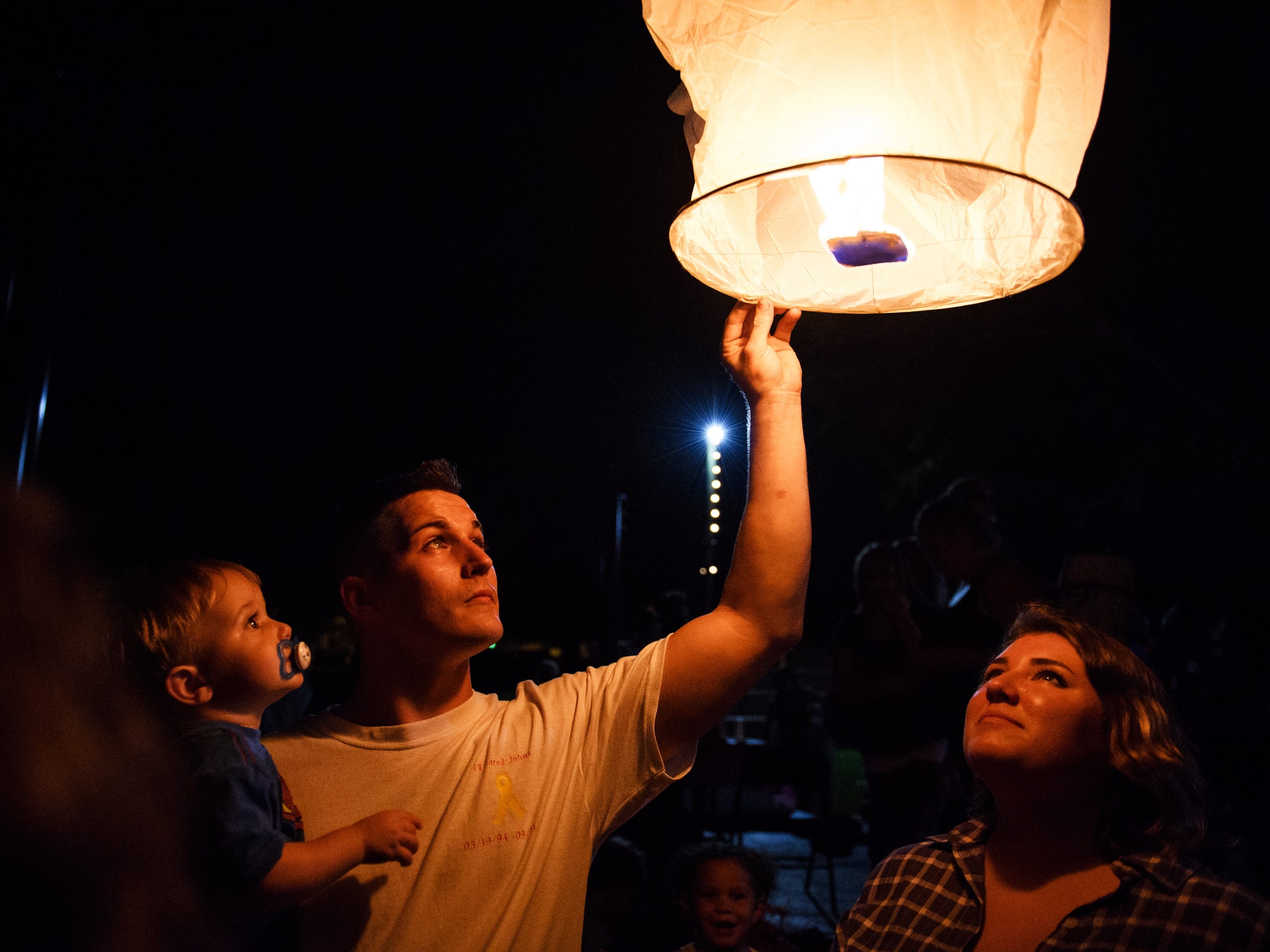 Jacob Johns holds his nephew, Jaxson, 1, as he and his fiancee Paige Torres release a paper lantern in honor of Jacob's twin brother Jared at Simpsonville City Park on Sunday, Sept. 23, 2018. Jared Johns, the father of Jaxson and a veteran of the U.S. Army, suffered from PTSD and died by suicide on Tuesday, Sept. 11, 2018.