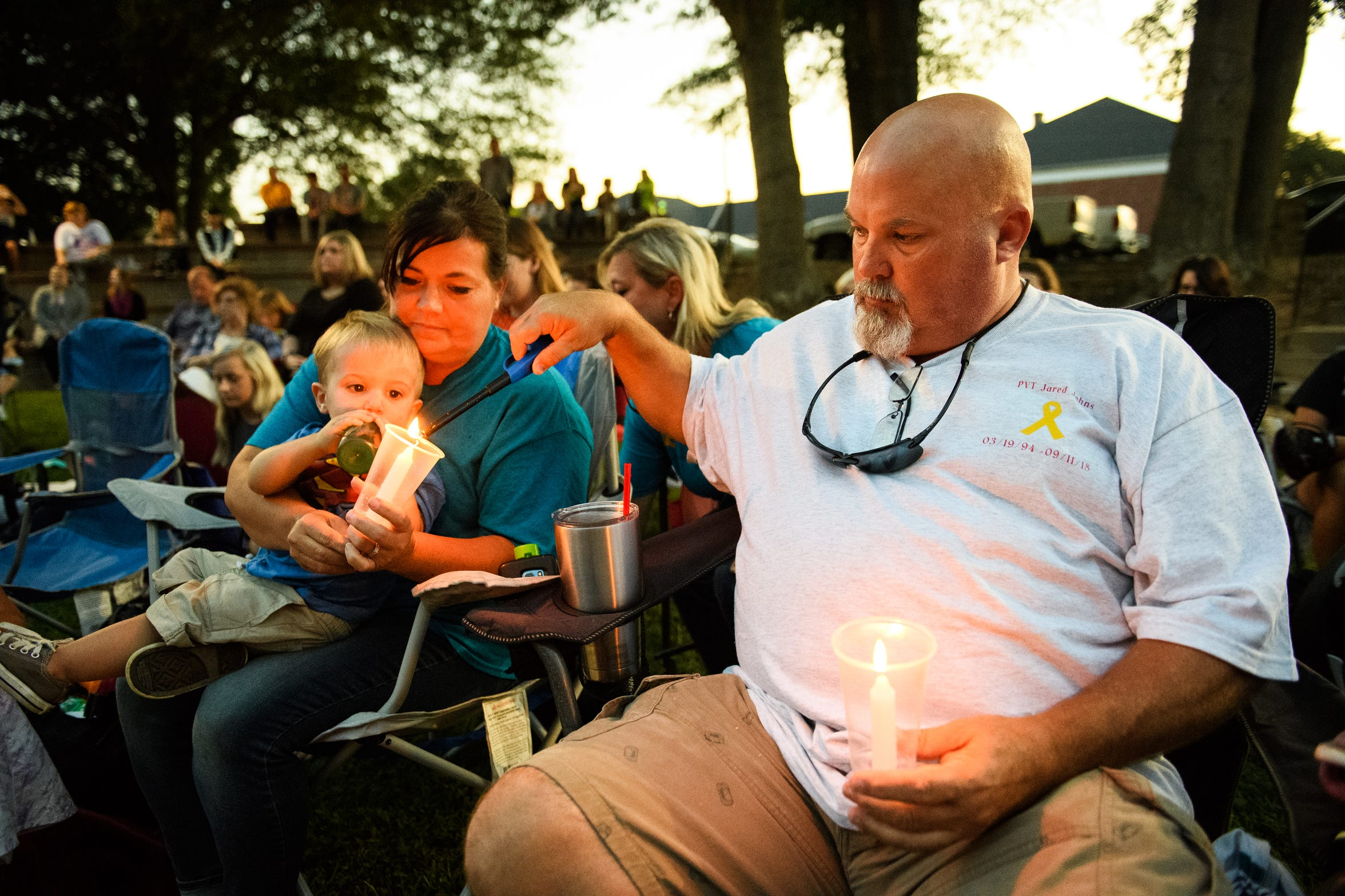 Kevin Johns, lights a candle for Kathy Bowling during a candlelight vigil for their son Jared Johns at Simpsonville City Park on Sunday, Sept. 23, 2018.