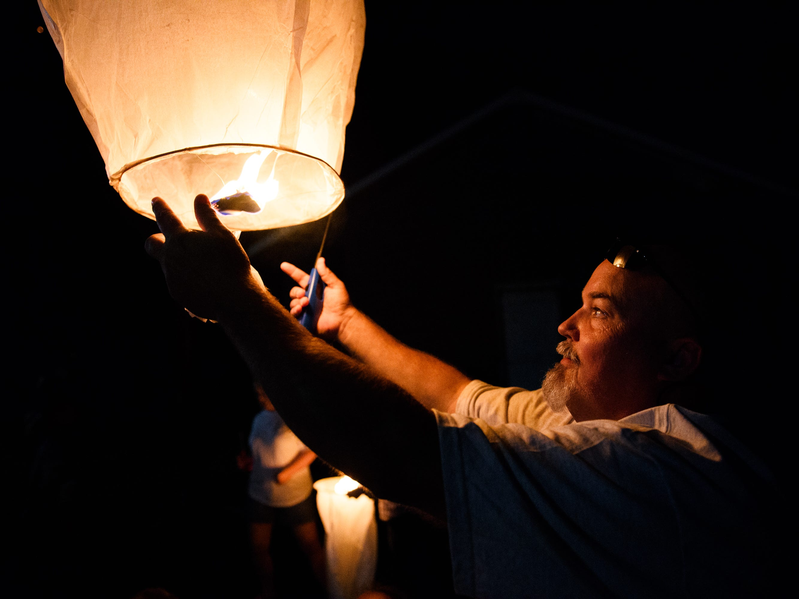 Kevin Johns releases a paper lantern into the air during a vigil for his son, Jared, at Simpsonville City Park on Sunday, Sept. 23, 2018.