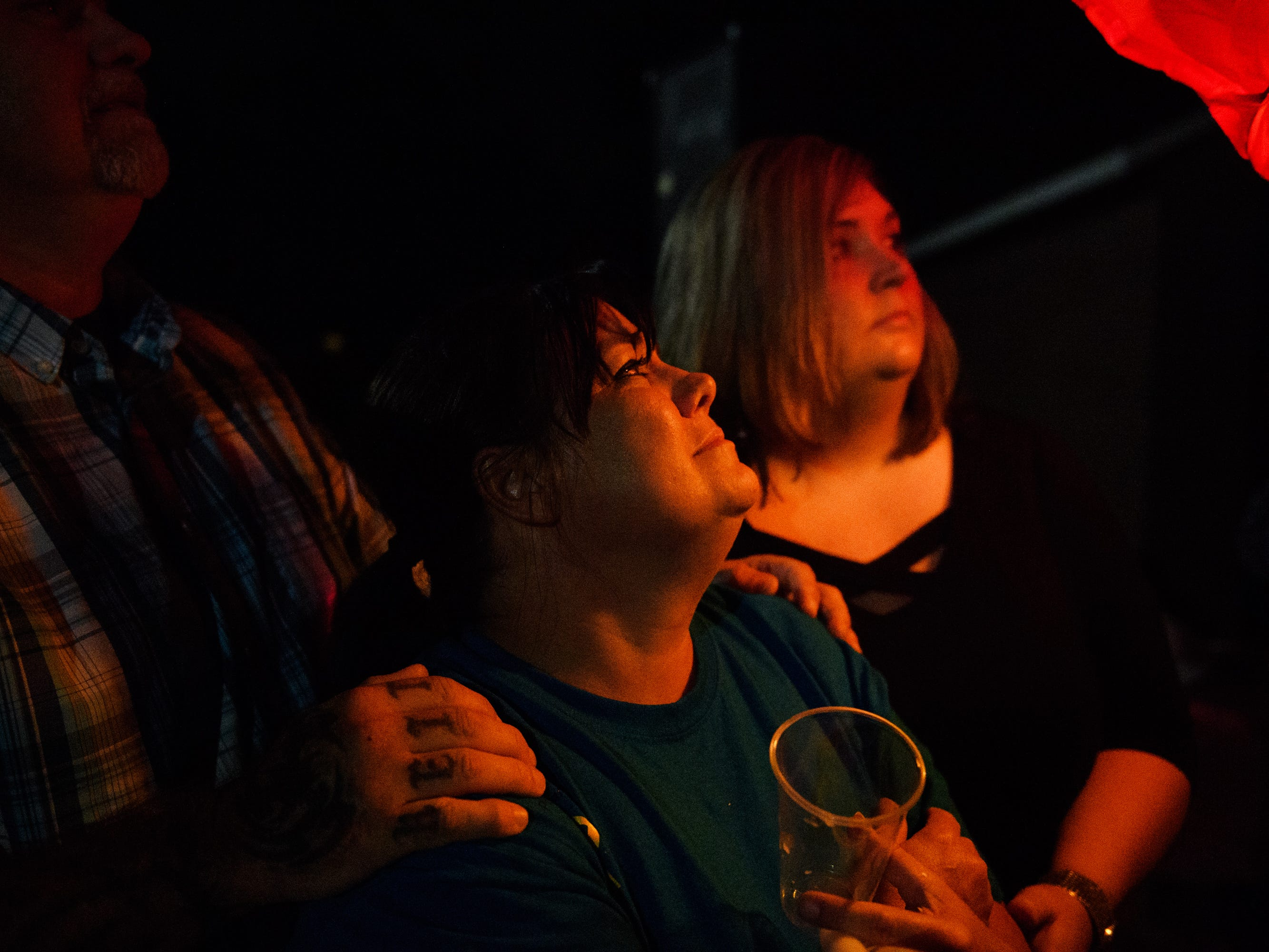 Kathy Bowling is comforted by her brother Keith Payne and his wife Erica as she watches a paper lantern float into the sky during a vigil for her son Jared on Sunday, Sept. 23, 2018.