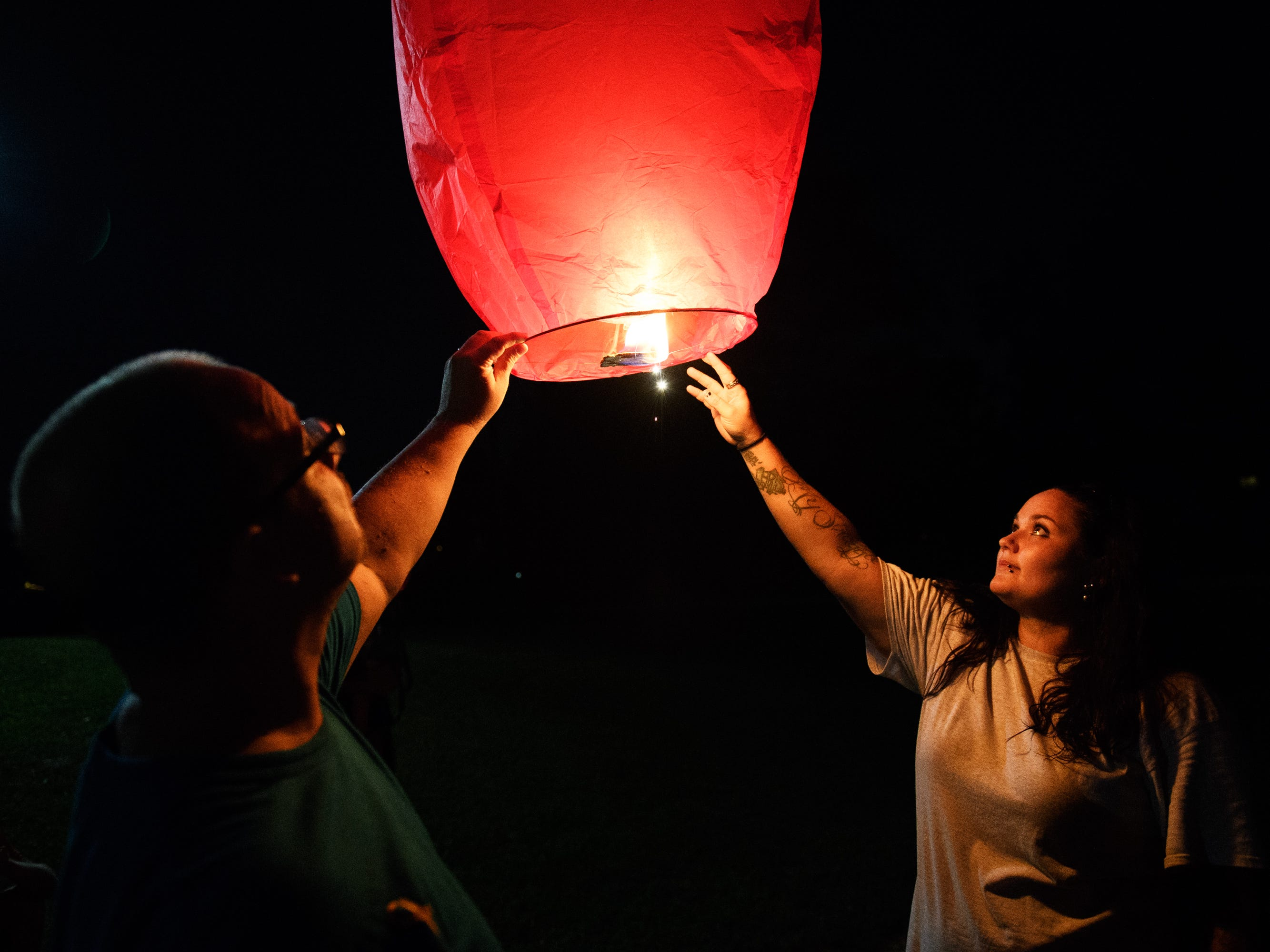 Kimilee Johns and Gary Bowling release a paper lantern into the air during a vigil for Kimilee's brother, Jared, at Simpsonville City Park on Sunday, Sept. 23, 2018.