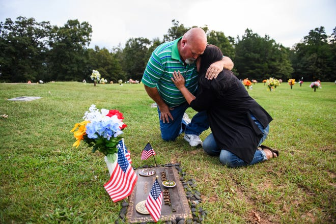 Kevin Johns comforts Kathy Bowling at their son Jared Johns' grave at Cannon Memorial Park on Thursday, Sept. 27, 2018. Jared Johns, a U.S. Army veteran who suffered from depression due to PTSD, died by suicide on Tuesday, Sept. 11, 2018.