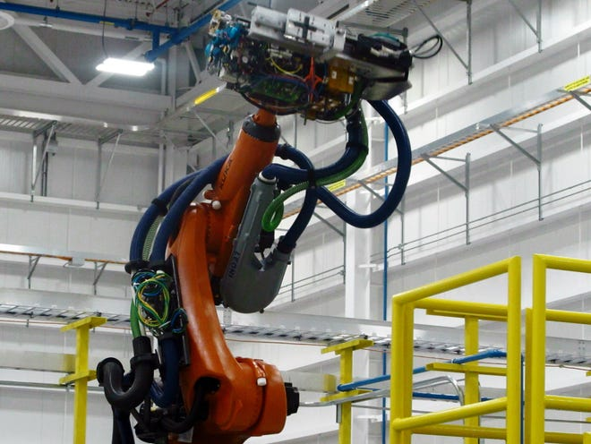 A prototype of a robot that will be used in Boeing's Propulsion South Carolina plant to manufacture jet engine intakes is displayed after the plant opened on Wednesday, Feb. 11, 2015, in North Charleston, S.C. Boeing announced that the plant, although just opening, has been assigned new work in addition to building engine air intakes for the company's new 737 MAX,  a new generation of Boeing's workhorse 737. (AP Photo/Bruce Smith)