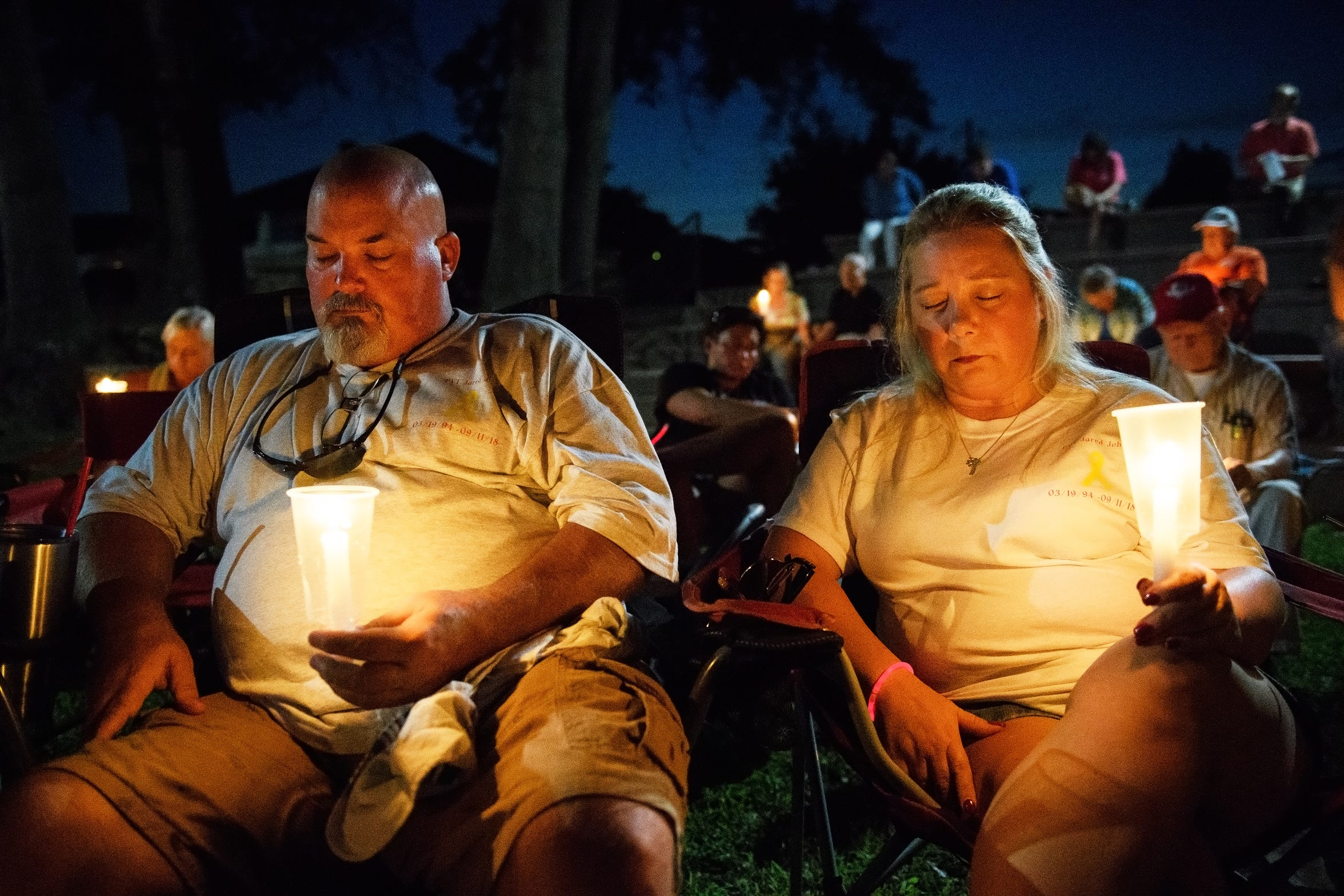 Kevin Johns and his girlfriend Kim pray during a candlelight vigil for Kevin's son, Jared, at Simpsonville City Park on Sunday, Sept. 23, 2018.