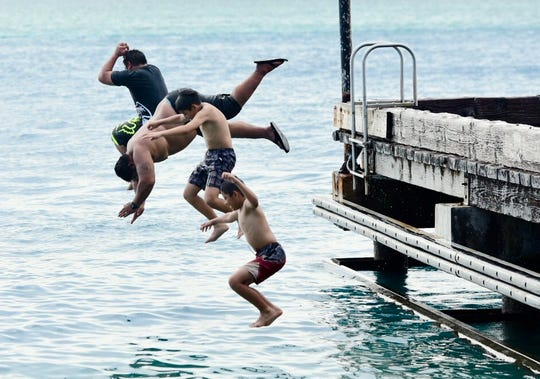 Children jump into the ocean from the Merizo pier in this Sept. 28, 2018, file photo.
