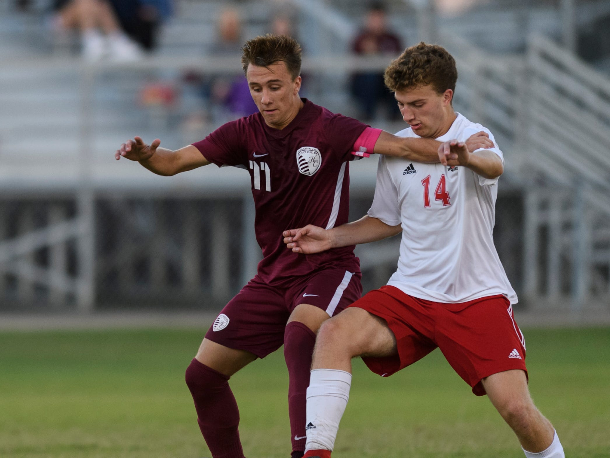 Henderson County's Max Wawrin (11) and Daviess County's Porter Watkins (14) fight for the ball at Colonel Field in Henderson, Ky., Thursday, Sept. 27, 2018. The Panthers defeated the Colonels 5-3.