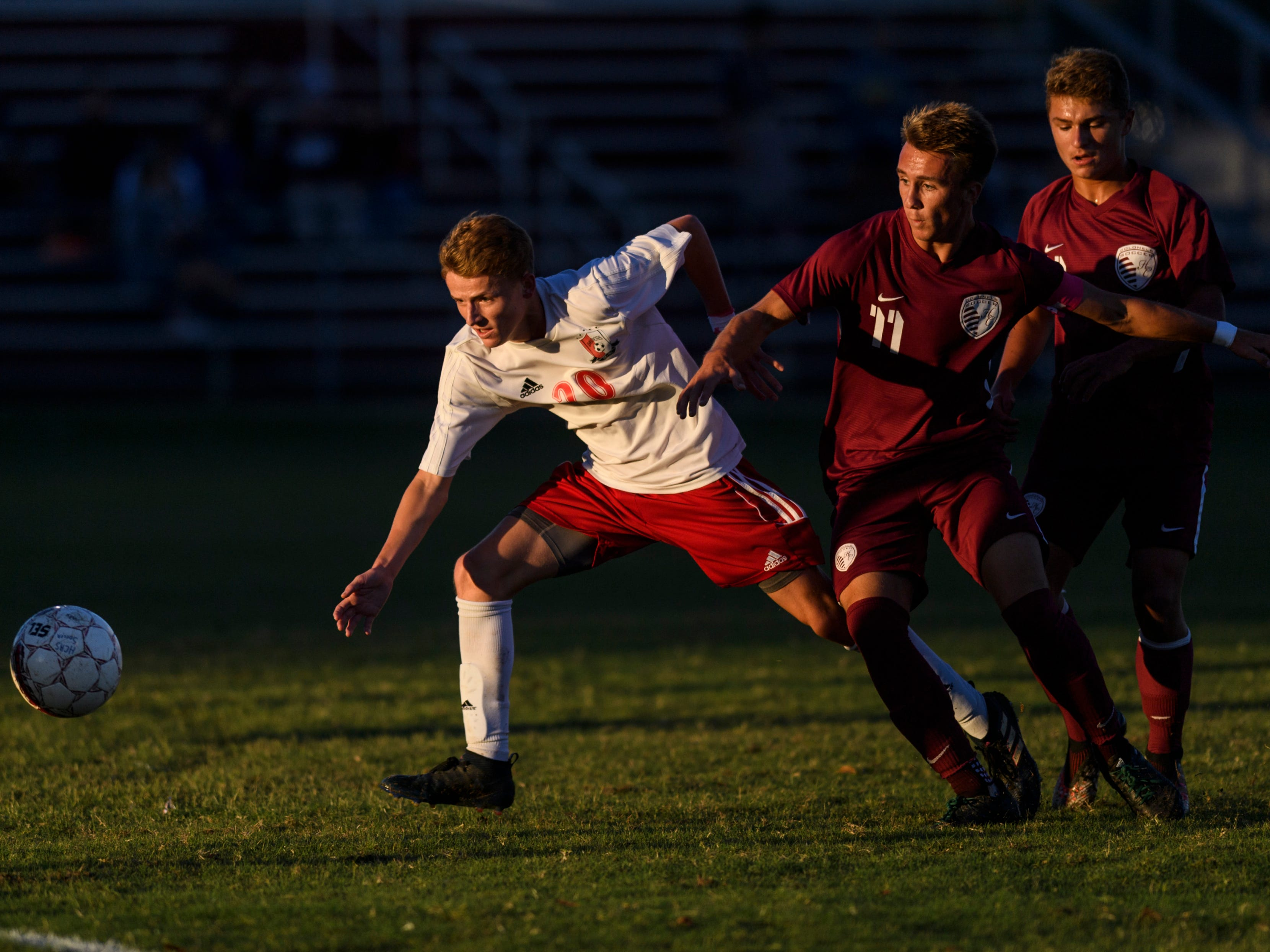 Daviess County's Jacob Boling (20) and Henderson County's Max Wawrin (11) fight for possession of the ball during the first half at Colonel Field in Henderson, Ky., Thursday, Sept. 27, 2018. The Panthers defeated the Colonels 5-3.