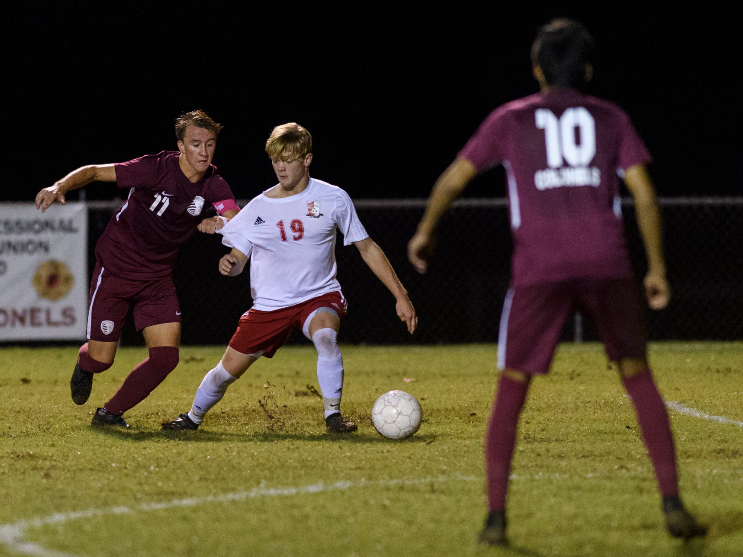 Henderson County's Max Wawrin (11) attempts to make a steal from Daviess County's Hayden Glover (19) during the second half at Colonel Field in Henderson, Ky., Thursday, Sept. 27, 2018. The Panthers defeated the Colonels 5-3.