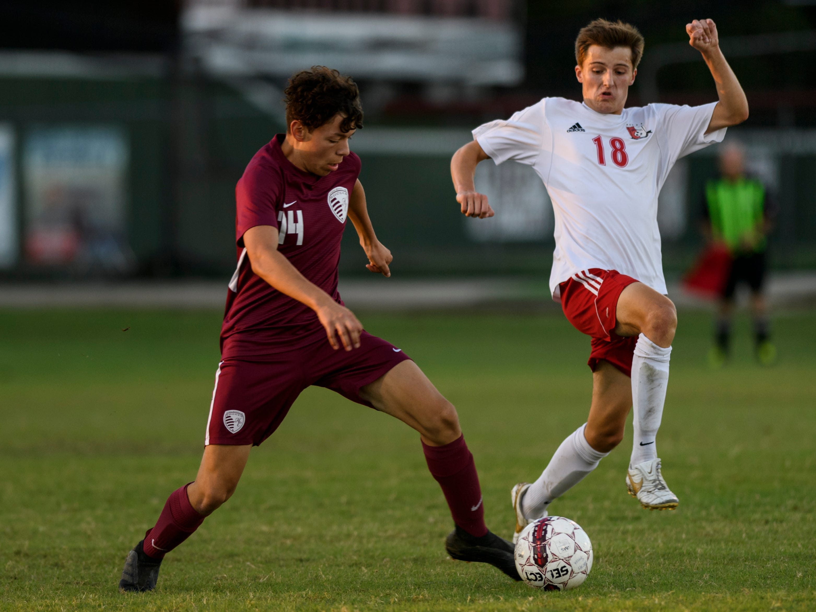 Henderson County's Jordan Toribio (14) keeps the ball from Daviess County's Declan Armistead (18) during the first half at Colonel Field in Henderson, Ky., Thursday, Sept. 27, 2018. The Panthers defeated the Colonels 5-3.