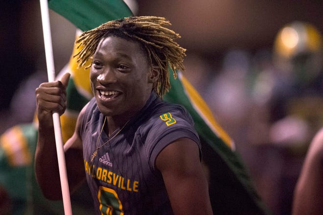 A team member of Taylorsville football runs a color flag after a touchdown against Bay Springs at Taylorsville High School. Thursday, Sept. 27, 2018.