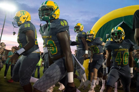 The Taylorsville High School varsity football team bursts onto their home field through a tunnel before a game against the Bay Springs Bulldogs. Thursday, Sept. 27, 2018.