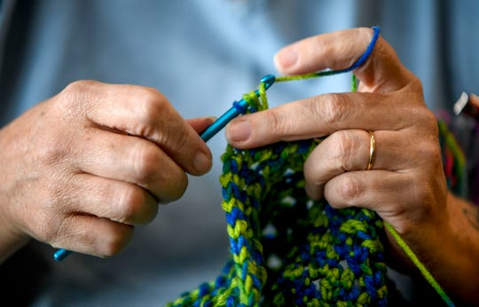 Rhonda Norres carefully weaves thread in and out of loops to crochet a backpack that will be given away to victims of sex trafficking at West Tennessee State Penitentiary in Henning, Tenn., on Wednesday, Sept. 26, 2018.