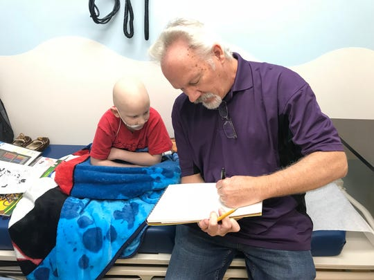 "John Rose draws ""Snuffy Smith"" for oncology clinic patient Lucas Salyers, 7, of Kingsport, on Friday at East Tennessee Children's Hospital. Rose has drawn the syndicated comic strip since 2001, after first assisting previous author Fred Lasswell."