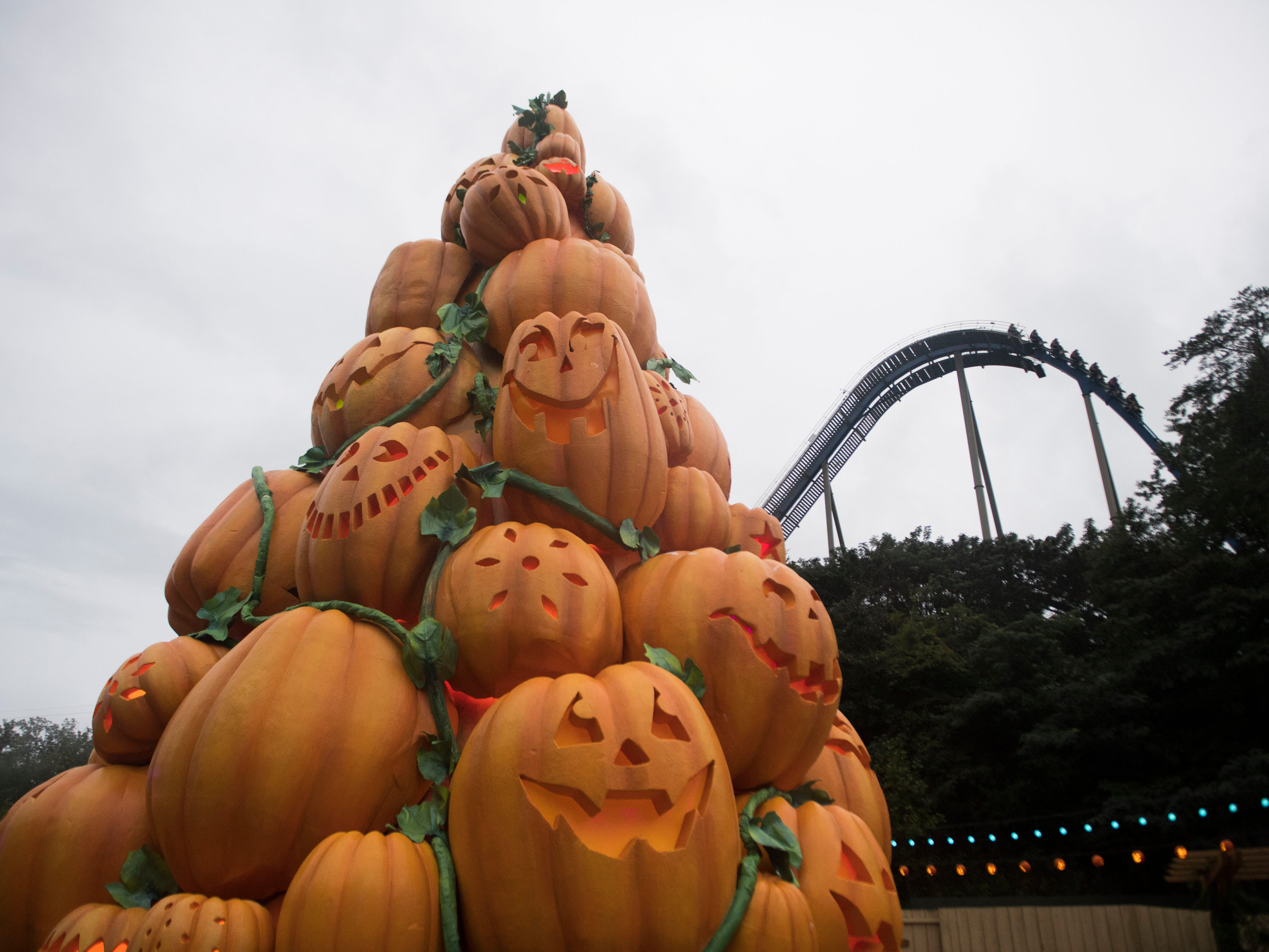 The Wild Eagle coaster at Dollywood runs in the background while a 40-foot pumpkin tower looms near it at Dollywood's second Great Pumpkin LumiNights festival in Pigeon Forge, Thursday, Sept. 27, 2018. The festival has doubled in size since last year.