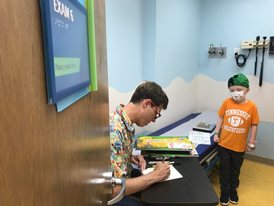 Anthony Owsley draws a Power T-wearing, football-toting robot for Vol fan Neyland Pickel, 8, of Athens, on Friday morning in East Tennessee Children's Hospital's hematology/oncology clinic.