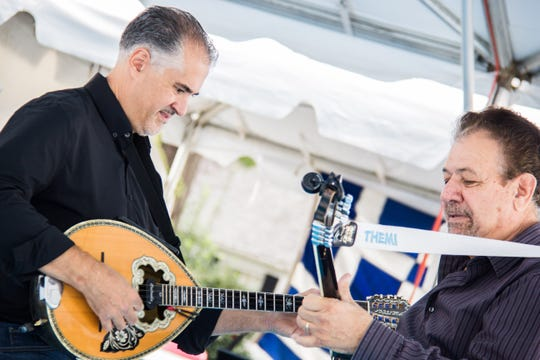 George Karras (left) and Themi Kakias, part of a three-piece band from Dayton, Ohio, play bouzoukis during the first day of Greek Fest on Sept. 28.