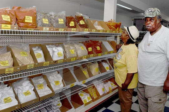 Customers Bisemark and Lois Duncan look over bags of seasoning in the butcher supply store at Targil.