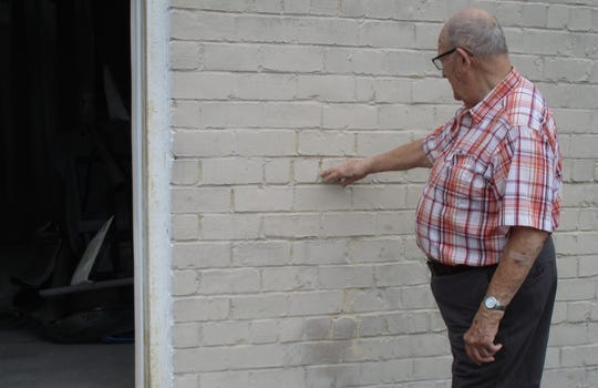 Dick Benadum is shown pointing out the stamped bricks on the west side of his company at 235 S. Columbus St. It was built in 1927 with bricks manufactured by prison labor at the state operated brick plant in Junction City.