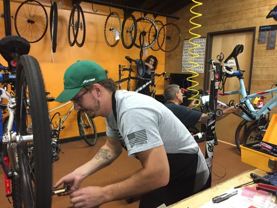 Hometown Bicycles employees, from left, Tyler Ostrowski, Kollen Van Alsburg and Bo Sporer work on bikes in the Brighton Township shop, Friday, Sept. 28, 2018.