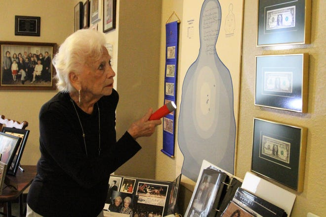 Marion Ellen Withrow shines a light on a series of bills marked with her signature. She holds a Guinness World Record for having her name on more than 68 billion bills during her time as the 40th Treasurer of the United States.