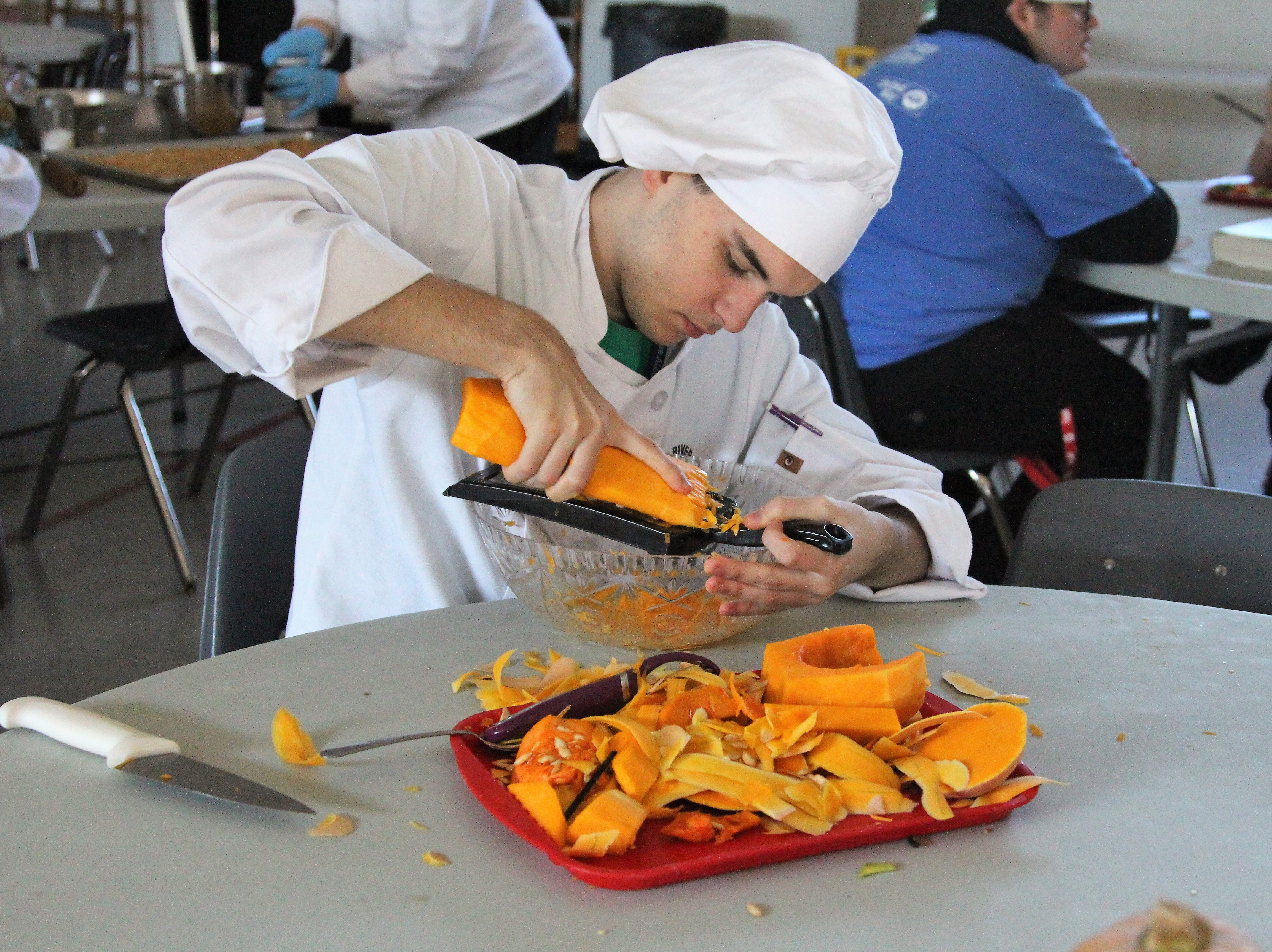 Tri-River's senior Caleb Ault grates a squash at the Salvation Army on Friday. He was one of 15 culinary students there that day.