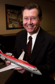 In this 2002 file photo, Philip H. Trenary, then-president and chief executive officer of Northwest Airlink.  He is holding a model of a Bombardier CRJ aricraft.