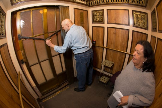 James Wodke opens the door of the elevator he operates.