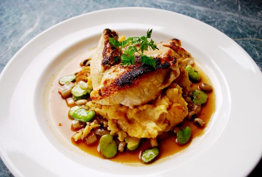 Roast chicken over smashed Yukon potatoes, fava and field peas and truffled jus at Ellington's Midway Bar & Grill, inside the Fairlane Hotel.