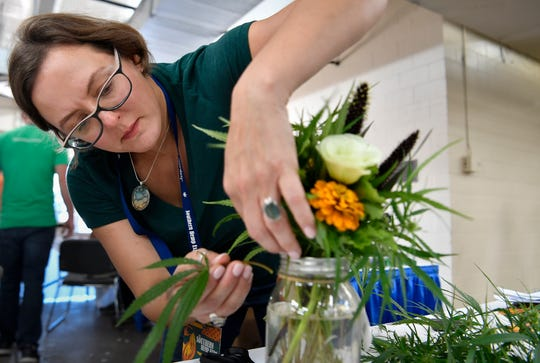 Cecily Friday, co-founder of the Southern Hemp Expo, makes a flower arrangement using a hemp plant Friday, Sept. 28, 2018, at The Fairgrounds Nashville.
